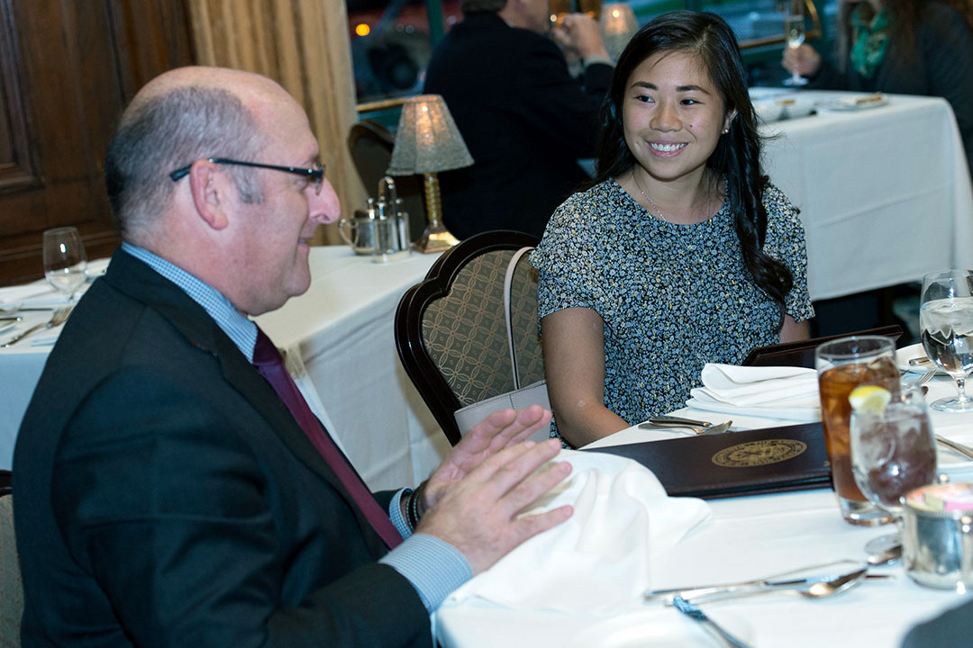 Alumnus speaks with current student at dinner