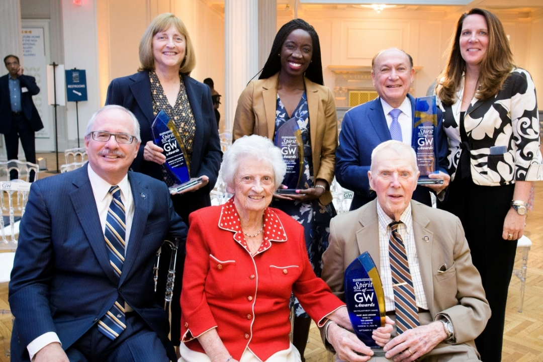 Group of award recipients gather with university leadership for photo at awards ceremony.