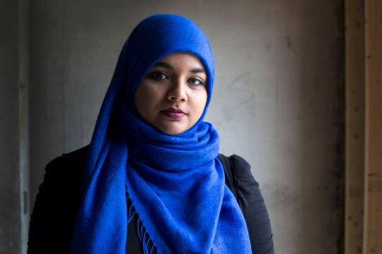 Muslim woman wearing blue head scarf poses for portrait in front of gray wall.